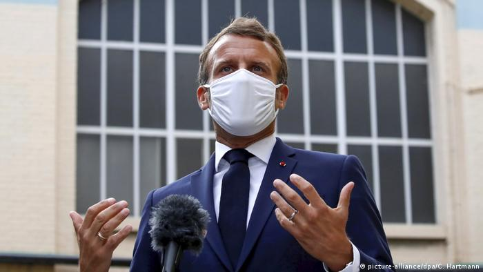 Emmanuel Macron mit Maske vor einem Mikrofon (picture-alliance/dpa/C. Hartmann)