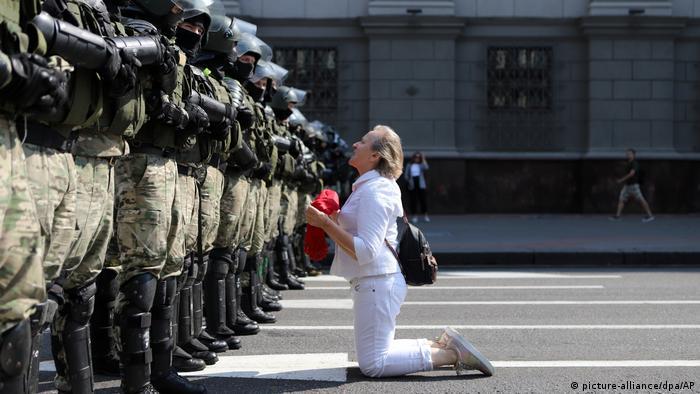 Женщина в белом стоит на коленях перед силовиками на проспекте Независимости в Минске