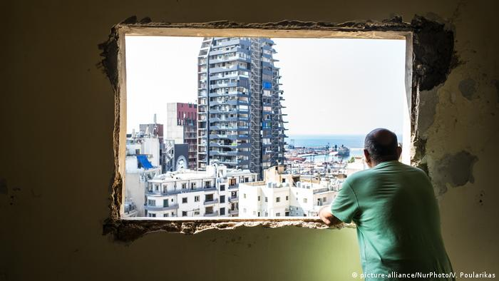 A Lebanese man gazes out of the window of his destroyed house to the area near where the explosion took place