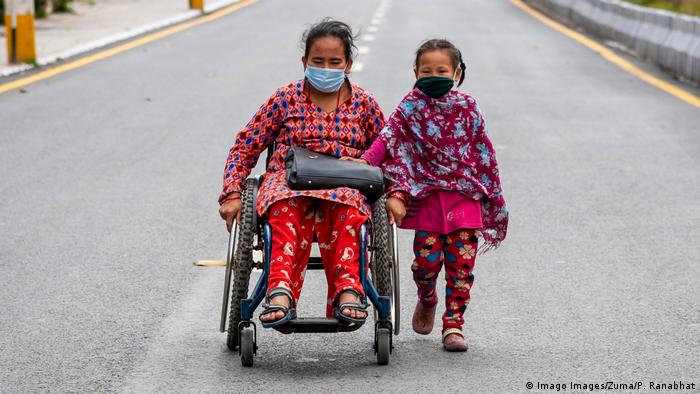 Shanti tamang, aged 32, in a wheelchair with her child, Rima tamang moving along a deserted road while wearing face masks as a precaution during lockdown