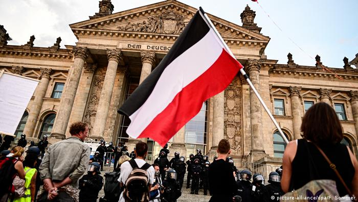 Participants at a protest against coronavirus restrictions stand with a nationalist flag in front of the Reichstag in Berlin