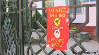 Плакат с предупреждением о масочном режиме в Алма-Ате