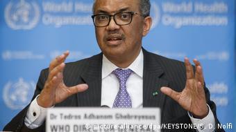 Tedros Adhanom Ghebreyesus, diretor-geral da Organização mundial de Saúde (OMS), sobre fundo azul com o logotipo da entidade.
