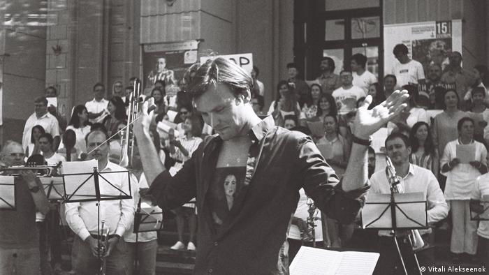 Vitali Alekseenok steht ovr der Philharmonie vor seinem Orchester und verbeugt sich Richtung Publikum