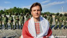 Vitali Alekseenok, flag around his shoulders, a row of soldiers behind barbes wire in the background