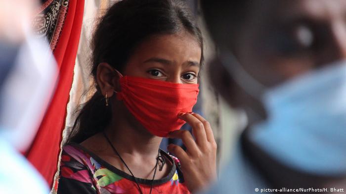 Indien Mumbai | Coronavirus: Mädchen mit Mundschutz beobachtet medizinisches Personal