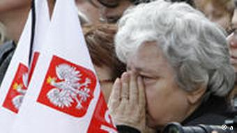 A woman covers her face during a national memorial service in Pilsudski Square in Warsaw