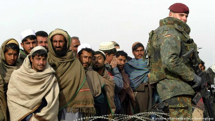 A German soldier securing a base standing in front of a group of Afghans