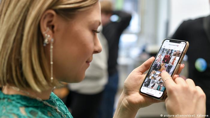 Mulher olha fotos no celular