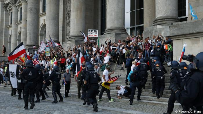 a mob with flags are stopped by police from entering a building