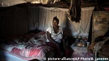 A female sex worker sits on a bed. (picture-alliance/AP Photo/B. Janssen)