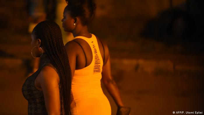 Prostitutes stand walk on the street in Benin City, capital of Edo State, southern Nigeria