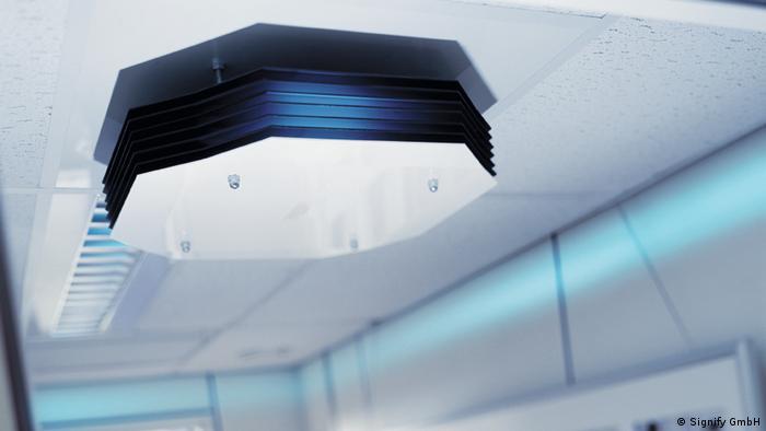 Simulação de uma lâmpada UVC em funcionamento, com faixa ultravioleta na altura do teto representada em cor azul