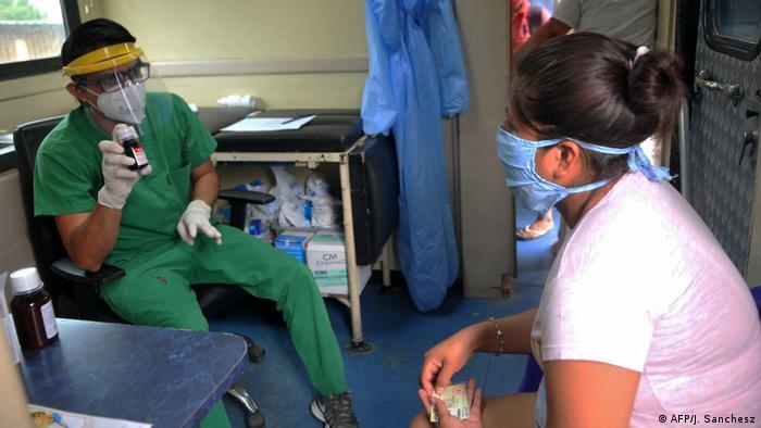 EcuadoUn médico provee asistencia a una trabajadora de salud en Guayaquil, Ecuador.