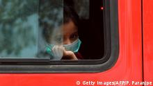 A child looks out from a bus window which is transporting migrant workers outside the Chhatrapati Shivaji Maharaj Terminus railway station to return to their hometowns after the government eased a nationwide lockdown as a preventive measure against the COVID-19 coronavirus, in Mumbai on May 19, 2020. - The lockdown affecting 1.3 billion people-the worlds largest-has been in force since late March and has been devastating for Indias poor with millions of migrant workers losing their jobs. (Photo by PUNIT PARANJPE / AFP) (Photo by PUNIT PARANJPE/AFP via Getty Images)