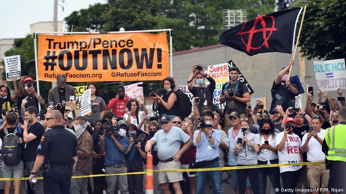 道路两旁聚集着特朗普总统的支持者和反对者