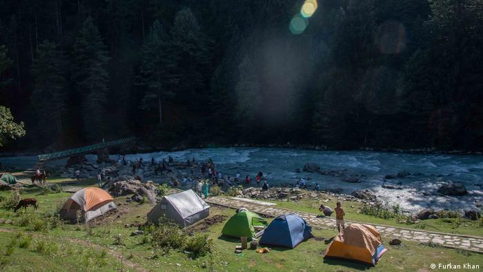 People camping by a river in the forest