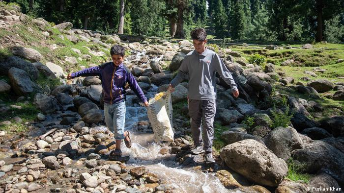 Two boys carry bags of trash down from local waterfall