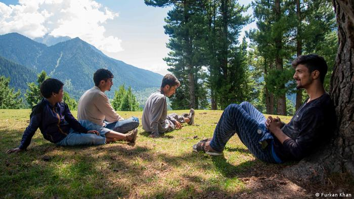Four boys sit in the shade of a tree. Mountains are visible in the distance