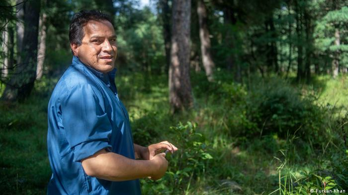 A man in blue clothing stands in front of some trees