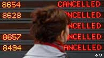 A passenger looks at a departure board filled with cancellations at a Paris airport