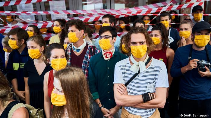 Protesting students wearing a yellow face mask