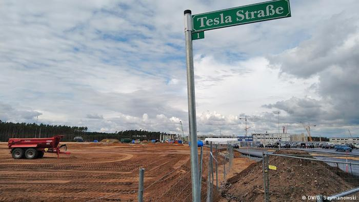 A road sign readying Tesla Street close to the entrance to the construction site of the Tesla factory in Grünheide