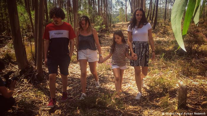 Four youth activists walk in woods in Portugal