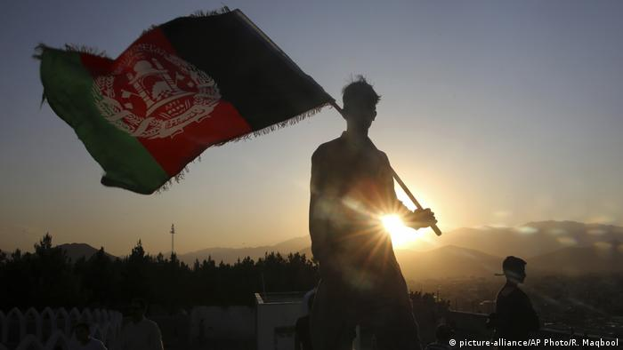 A man waves an Afghan flag during Independence Day celebrations in Kabul