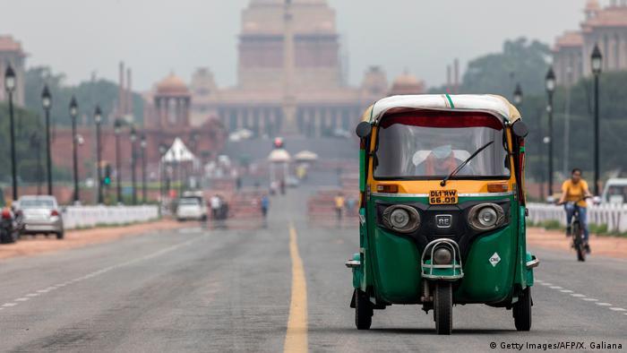 An auto rickshaw drives along a deserted Rajpath road in New Delhi