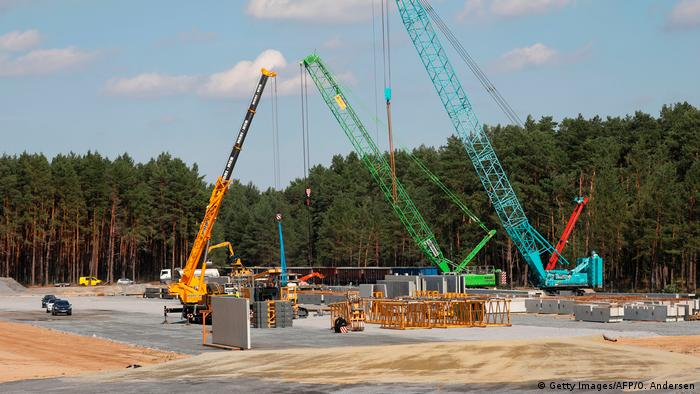 Cranes moving prefabricated concrete slaps around at the Tesla factory constuction site in Grünheide