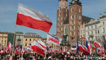 crowds of mourners waving polish flags in front of the Basilica of Our Lady in Krakow