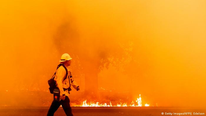 A firefighter walks against a bright orange backdrop of fire