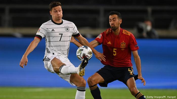 Игрок сборной Германии по футболу Юлиан Дракслер в борьбе за мяч с испанцем Серхио Бускетсом во время матча Лиги наций 3 сентября 2020 года