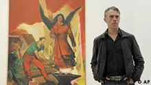 In this picture taken April 15, 2010, German painter Neo Rauch is seen in front of his painting 'Morgenrot' (Red Sunrise) in his exhibition 'Neo Rauch. Begleiter' (Neo Rauch. Companion) in the Museum of Fine Arts in Leipzig, central Germany. The exhibition is the first big retrospective about the painter of the Leipzig School and takes place in cooperation with the Pinakaothek der Moderne in Munich. Some 60 artworks are displayed, some of which for the first time, starting on April 18, 2010 until Aug. 15, 2010. (AP Photo/Jens Meyer)