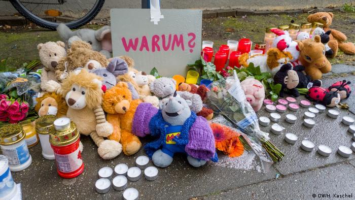 Por quê?, questiona uma placa em alemão, entre velas, flores e bichinhos de pelúcia dispostos no chão