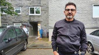 A man in a dark gray jacket in front of a housing complex in Solingen (DW/H. Kaschel)