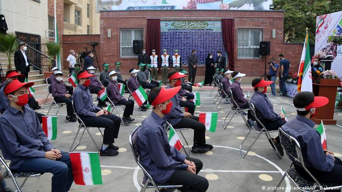 Iranian students practice social distancing while seated in the school grounds