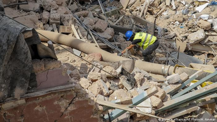Rescuers search at the site of a collapsed building in Beirut