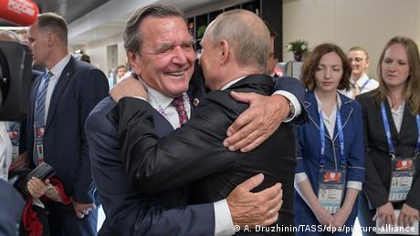 Gerhard Schröder und Vladimir Putin embracing each other
