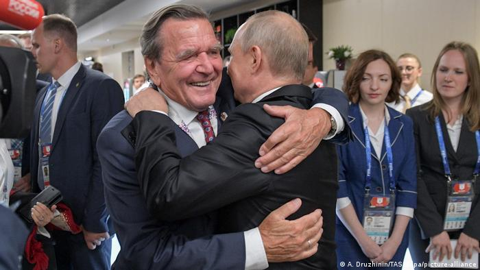 Former German Chancellor Gerhard Schroeder and Russian President Vladimir Putin hug at the opening of the 2018 FIFA World Cup in Moscow