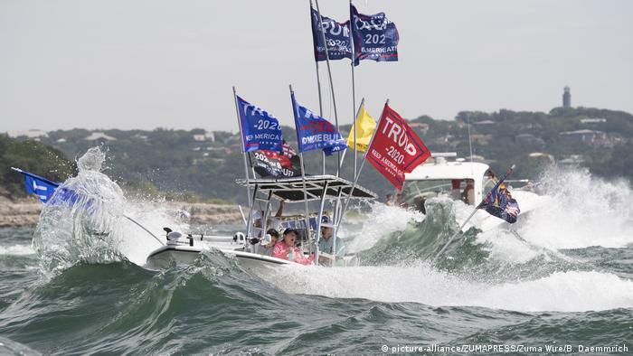 Barco com bandeiras de campanha de Trump em meio a ondas no lago Travis