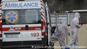 Врачи в защитных костюмах и микроавтобус скорой помощи в Киеве