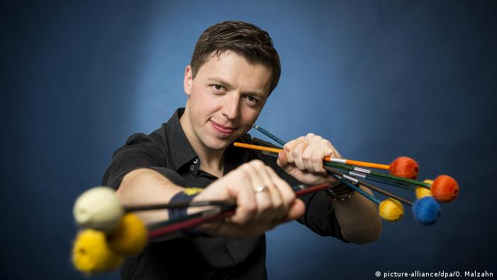Martin Grubinger holds a colorful array of drumsticks
