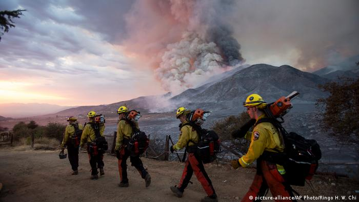Firefighters walk along a road as smoke rises from a mountain range in the background