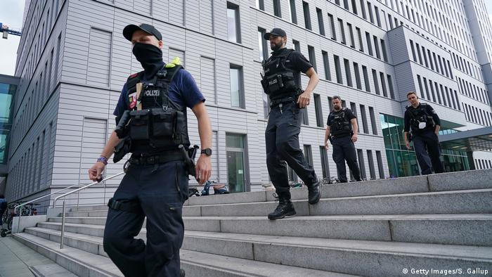 Polizisten in schwarzen Uniformen gehen eine Treppe vor der Berliner Universitätsklinik Charité herunter | Polizisten vor der Charité (Getty Images/S. Gallup)