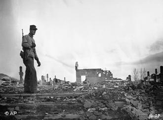 Marine Sgt. William T. Hathaway of Danville, Virginia, looks over the wreckage of Hanjung, Korea, Dec. 20, 1950, before the withdrawal from that city by U.N. forces now compressed into the Hungnam beachhead in northeast Korea. (AP Photo)