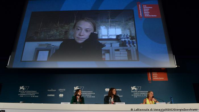 Greta Thunberg on a screen behind three panelists at the Venice Film Festival