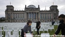 Activists set up chairs at the 'Platz der Republik' in front of the Reichstag building as part of the nationwide anti-racist action days of 'We'll Come United' in Berlin, Germany, Monday, Sept. 7, 2020. About some 13.000 chairs will be placed here in front of the parliament building, symbolising the people who currently live in Moria migrants camp in Greece. (AP Photo/Markus Schreiber)  