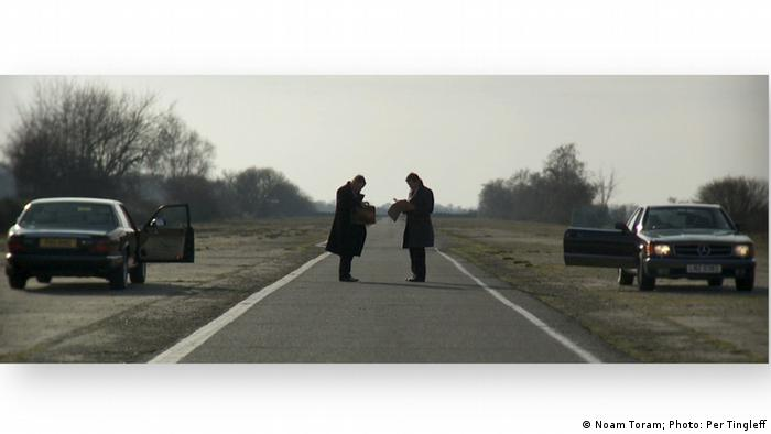 Two men stand in the middle of an empty road, facing one another, their cars behind them (Noam Toran; Photo: Per Tingleff)